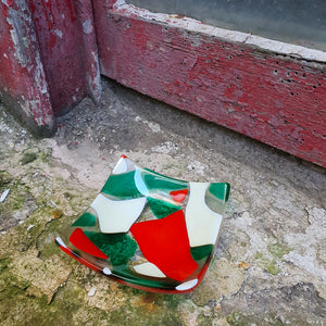 A fused glass trinket dish in red, emerald green, and French vanilla. Handmade by Connemara Blue