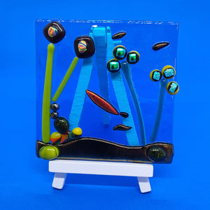 A fused glass miniature underwater scene with shiny dichroic glass and a mini easel for display. Handmade by Connemara Blue