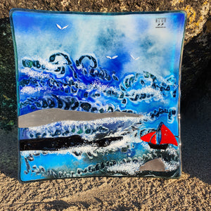 A fused glass plate featuring wild Atlantic waves, rocks and a Galway Hooker, handmade by Connemara Blue
