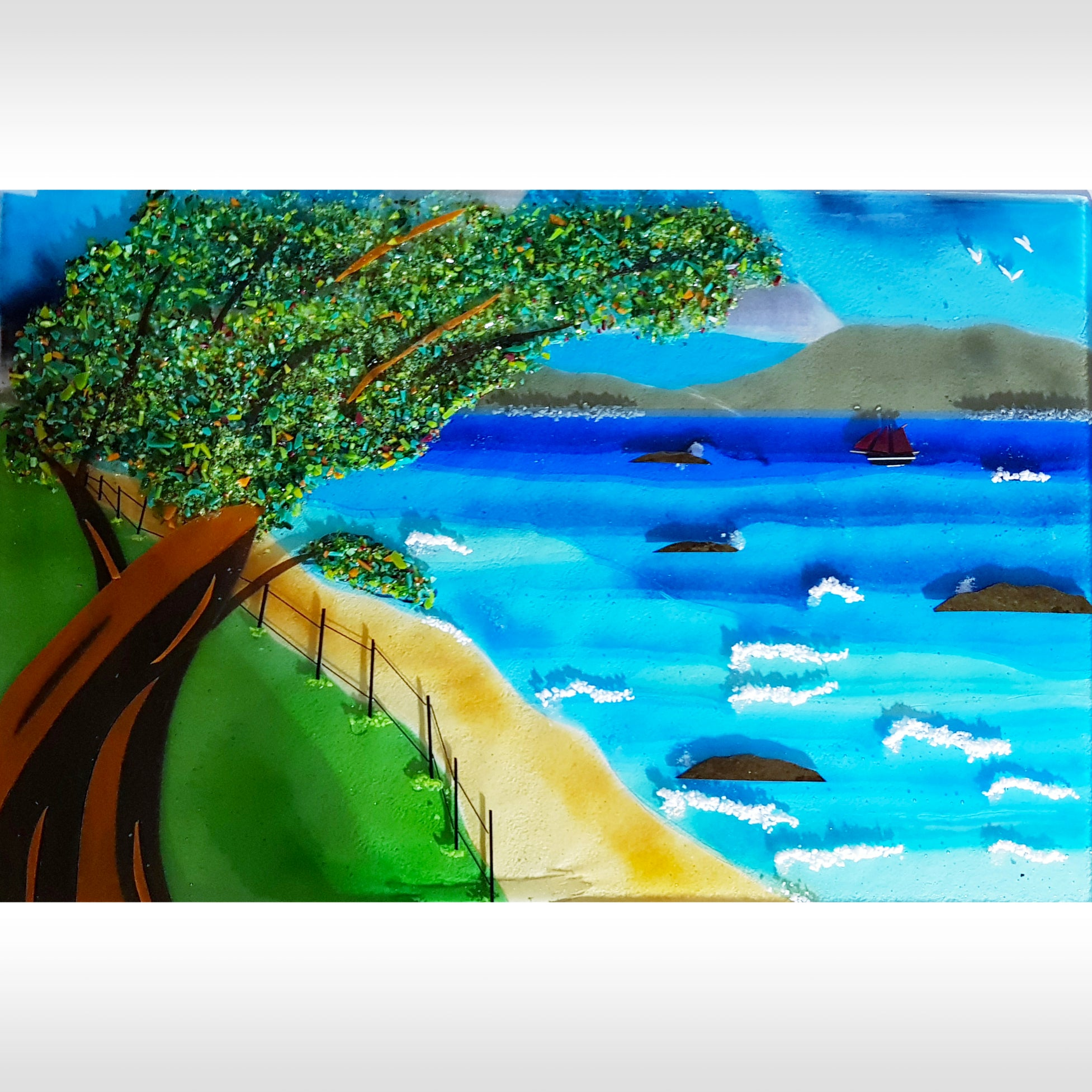 A fused glass wall panel from Connemara Blue featuring a windswept tree, beach, sea and mountains