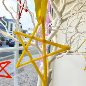 A yellow fused glass star decoration, handmade by Connemara Blue