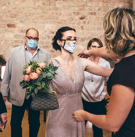 A lovely young bride holding a bouquet and wearing a cat-inspired face covering embraces a member of her wedding party.