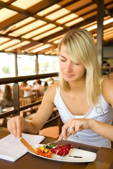 Beautiful young woman eating vegetarian food in a restaurant