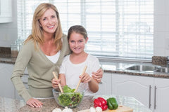 Mother and daughter preparing a salad