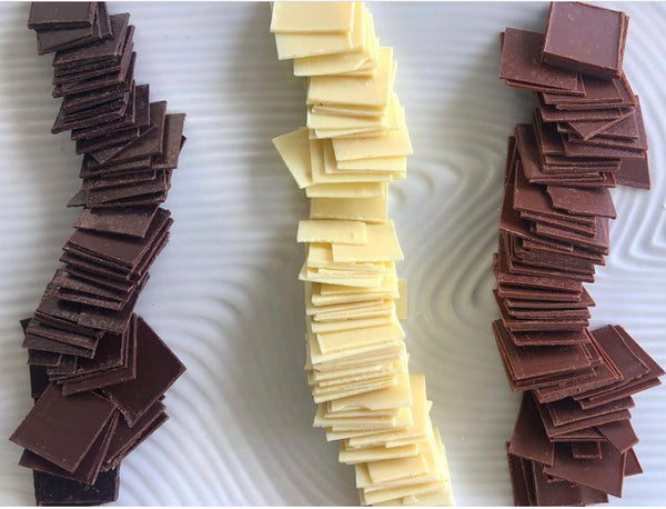 samples of craft dark, white and milk chocolate on a white plate