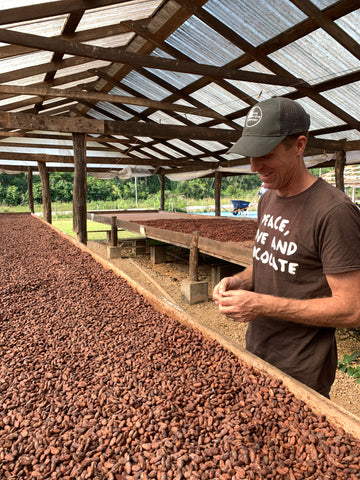 chris tasting dried cacao beans at Maya Mountain Cacao