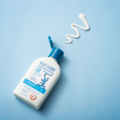 Blue Lizard Sensitive SPF 30+ Mineral Sunscreen with smear of product on blue background