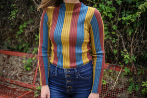 Long sleeve mock turtle neck top with mustard, rust, and blue vertical stripes