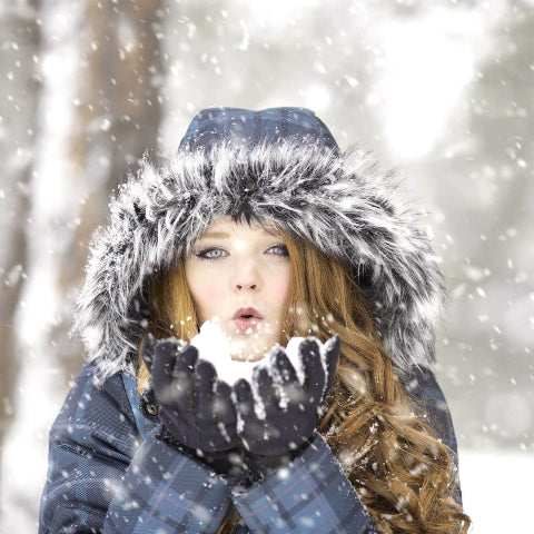 Girl blowing in snow