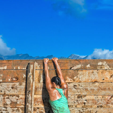 Woman climbing a wall and perspiring