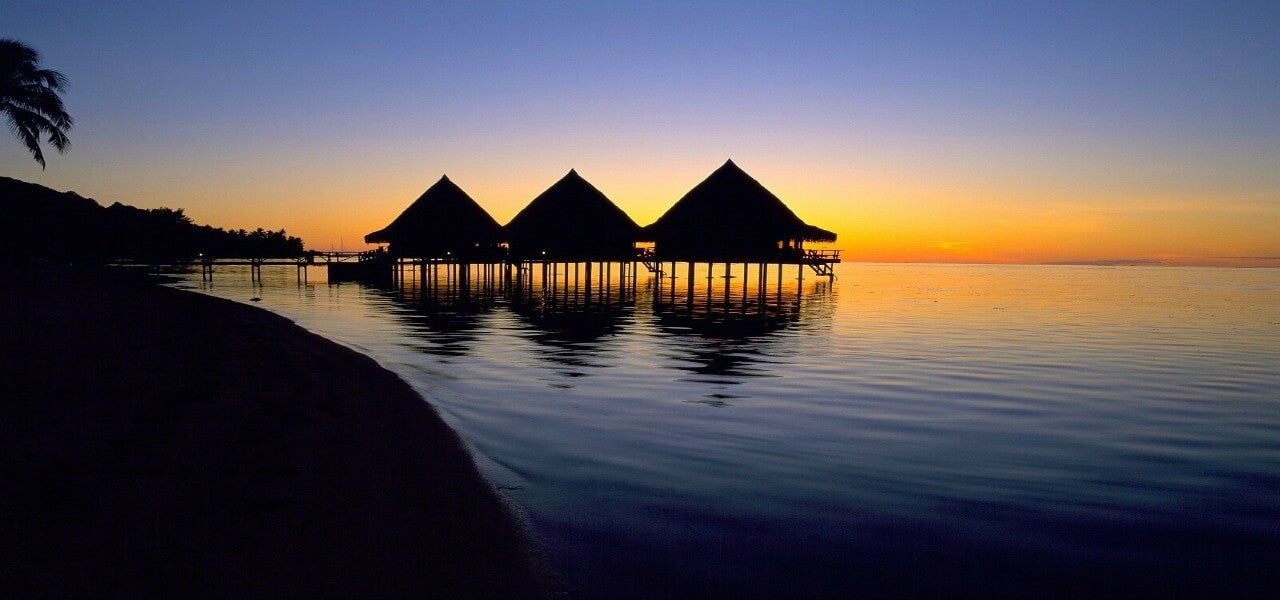 Image of luxury vacation huts on stilts at sunset above a plastic free ocean