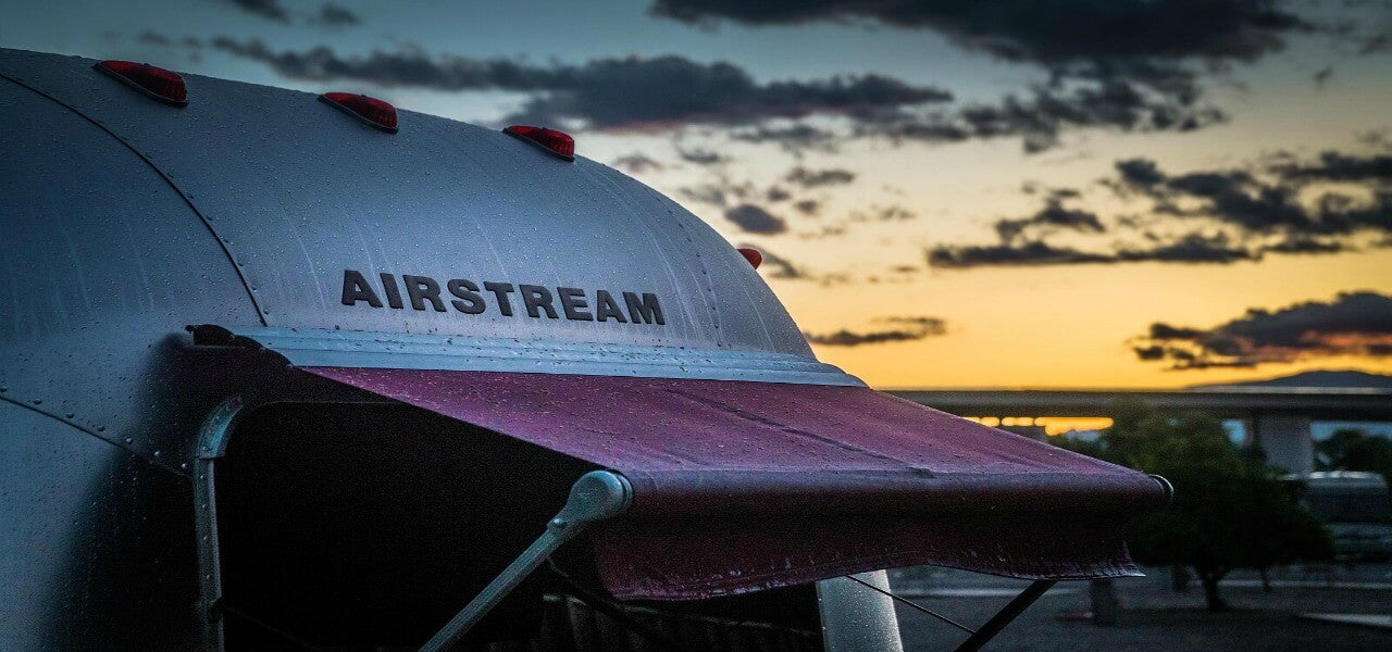 A silicon free Airstream mobile home against a sunset backdrop