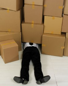 Image of a man squashed under boxes