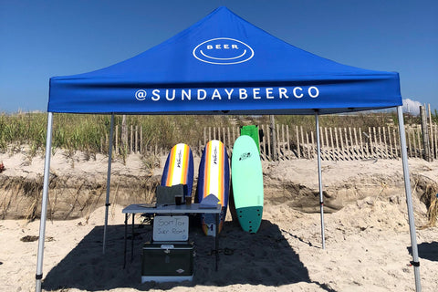 Blue branded Tent on beach with surfboards