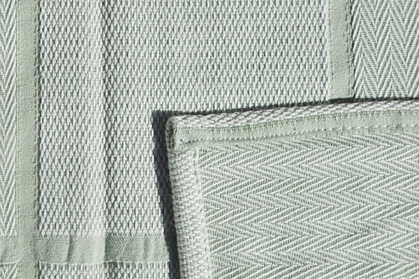 Abside green and white cotton blanket with corner close up