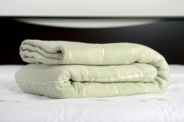 Abside oversized cotton blanket, green/white, folded on bed, Excess Comfort. Made in Portugal.