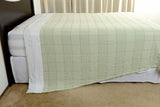 Unique blanket hog solution. Abside oversized cotton blanket, green/white, side hanging view for illustration. Excess Comfort, Made in Portugal.