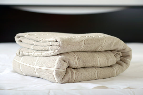 Abside oversized cotton blanket, linen/white, folded on bed, Excess Comfort. Made in Portugal.