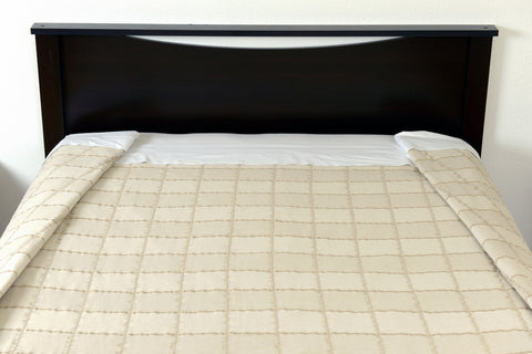Top foot end view with folds. Abside oversized cotton blanket, linen/white. Excess Comfort.