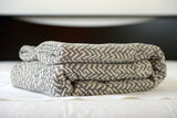 Best quality cotton blankets by Netting oversized cotton blanket, grey/ecru, folded on bed, Excess Comfort. Made in Portugal.