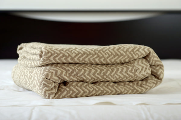 Netting oversized cotton blanket, linen/ecru, folded on bed, Excess Comfort. Made in Portugal.