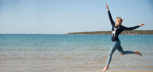 Girl jumping in Tallis jumper by the sea in Greece