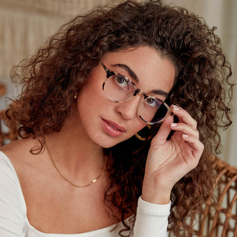 Young lady with long wavy hair on a wicker chair looking into the camera while wearing the Jaxson cream tortoise blue light glasses