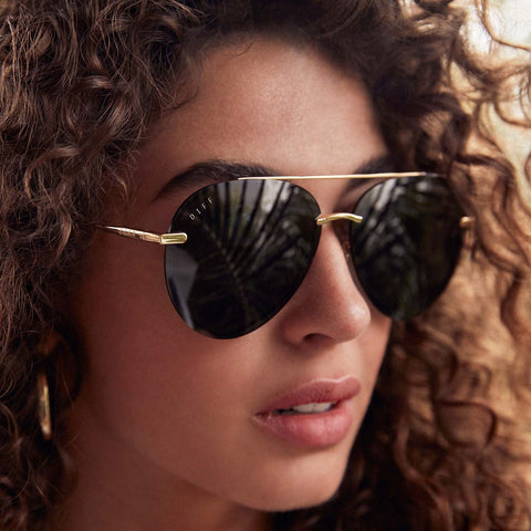 Close up portrait of woman with wavy hair looking into the distance wearing the Lenox Gold Aviator Sunglasses with blue lens
