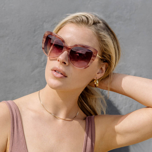 Young blonde woman standing against grey wall outside while holding her hair in a ponytail, wearing pink Avery Cassis frames with Wine Gradient