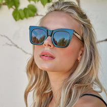 blonde model wearing the kaia black and grey polarized sunglasses