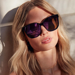 GIA sunglasses with black frames and pink mirror lens on model