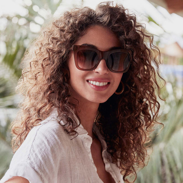 Young woman with long dark curly hair standing in front of distant palm trees and wearing Kaia Dark Taupe sunglasses with Brown Gradient Polarized lenses