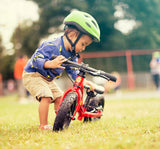 Child beside Frog Tadpole Mini Balance Bike in Red