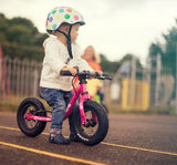 Child riding Frog Tadpole Mini Balance Bike in Pink