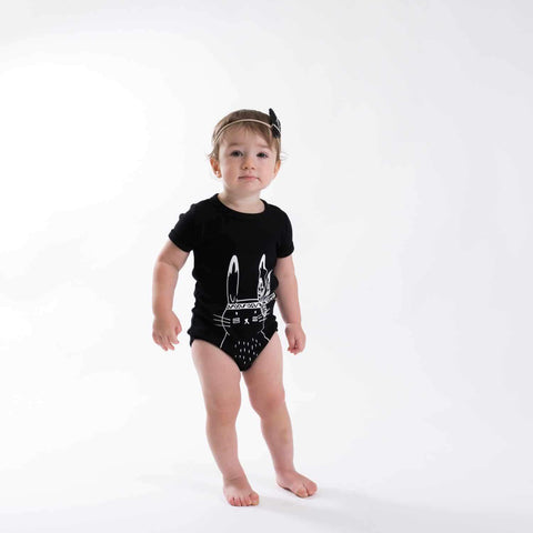 Little girl wearing the Black Aster & Oak Organic Cotton Bunny Chief Onesie