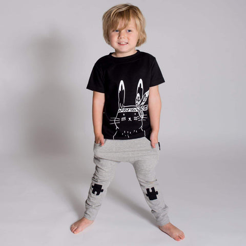 Little boy wearing the Black Aster & Oak Organic Cotton Bunny Chief T-Shirt and harem pants