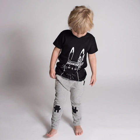 Little boy wearing the Aster & Oak Organic Cotton Bunny Chief T-Shirt in Black and grey harem pants