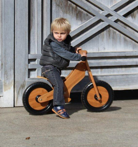 Little boy riding the Kinderfeets Bamboo Classic Balance Bike