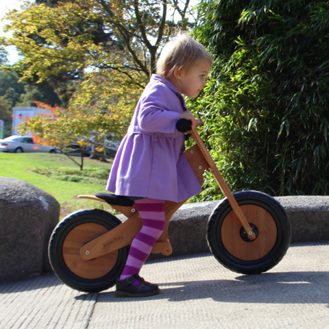 Little girl riding a Kinderfeets Classic Bamboo Balance Bike