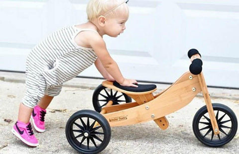 Little girl pushing her Kinderfeets Tiny Tots 2-in-1 Tricycle/Balance Bike in Bamboo as a tricycle