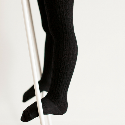 Child standing on a ladder wearing Lamington Merino Tights in Black cable-knit pattern