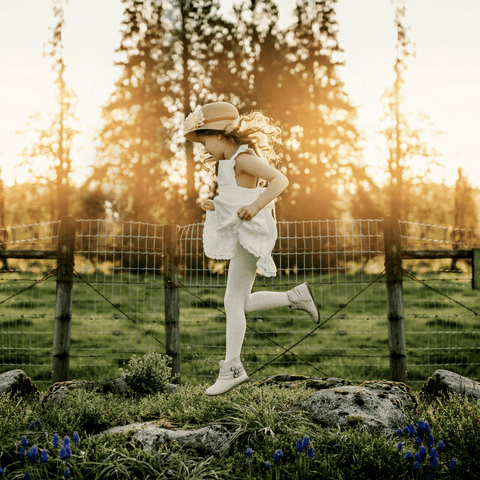 Little girl running in the grass wearing Lamington Merino Tights in Cream