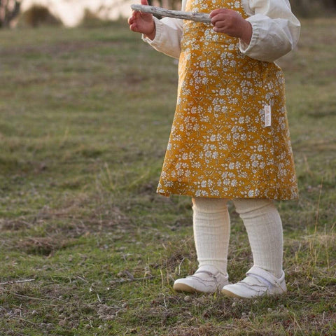 Toddler girl wearing Lamington Merino Tights in Cream cable-knit
