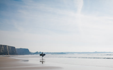 Surfer with an original Mackie Surfboard at Watergate Bay, Cornwall
