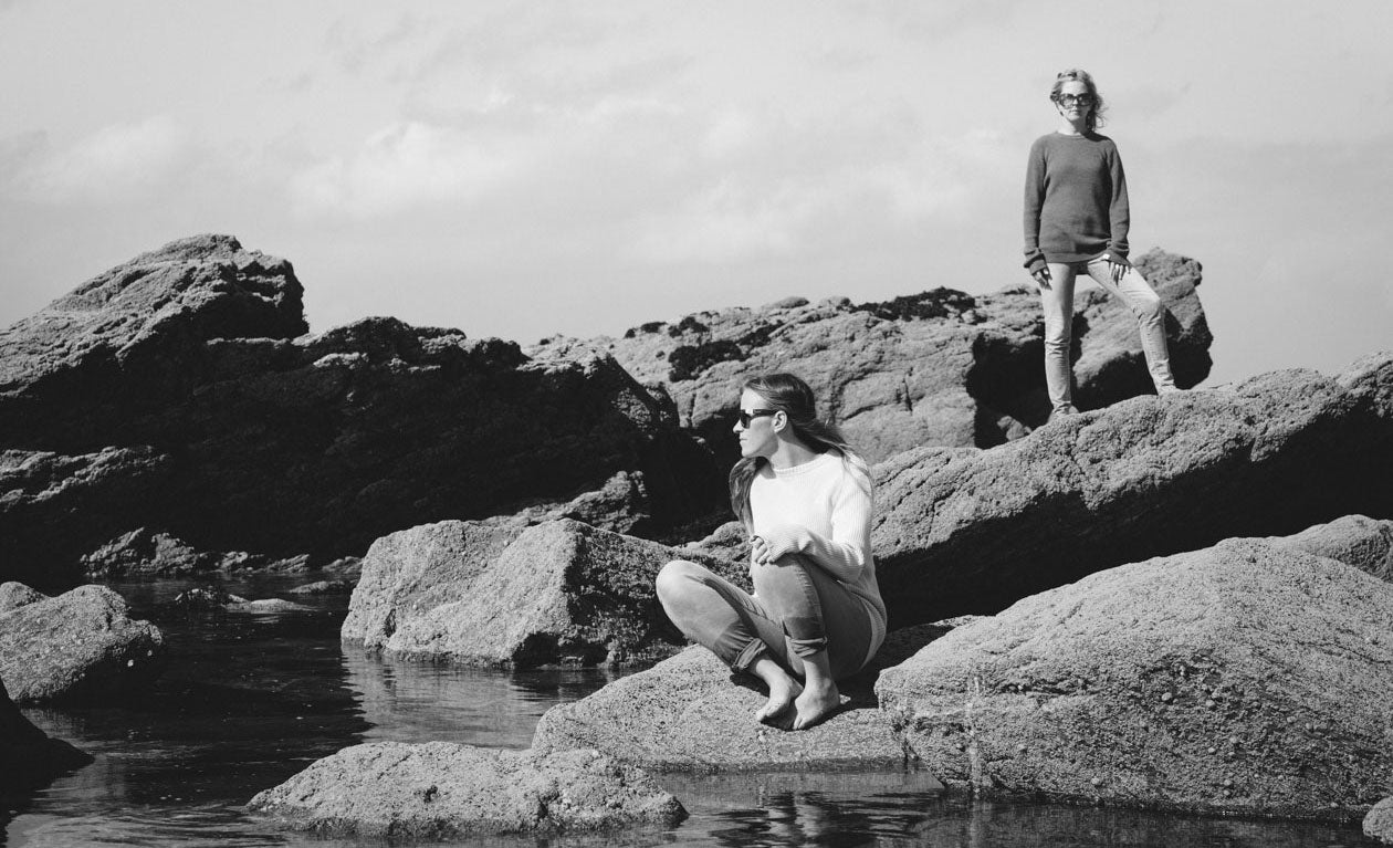 Models wearing Old Harry apparel sat in the rock pools