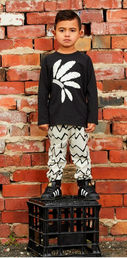 Hootkid Player Pant. Light grey marle trackpant with black linear pattern. Lifestyle image.