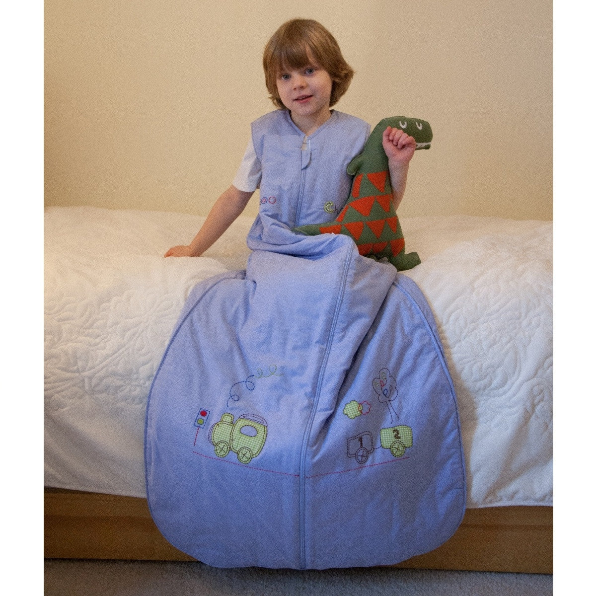 Sleeveless blue sleeping bag with centre zip.  Has train embroidery.