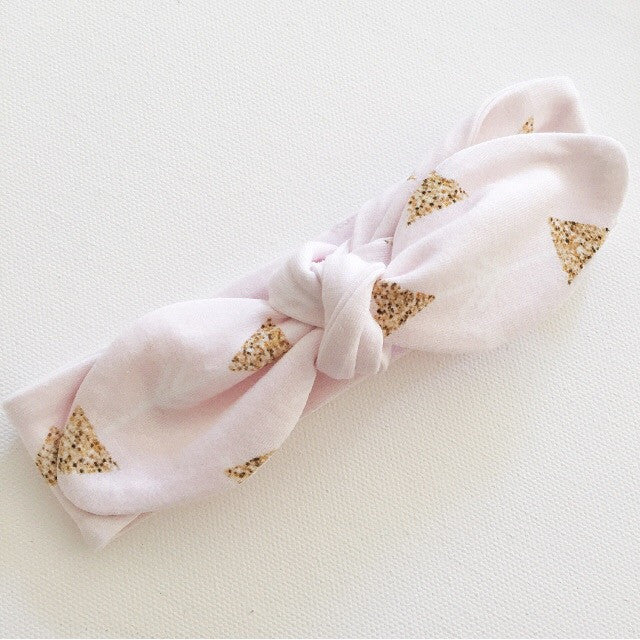 Palest pink headband with gold glittery triangles.