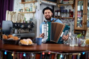Hipster cafe owner playing accordion at bar counter
