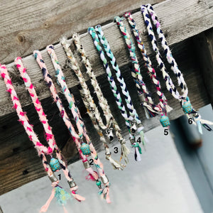 "Simply Summer Wraps are our favorite summer accessory.  These colorful wraps are handmade and totally unique.  Each colorful fabric necklace has different pendant and bead combinations.  Wear them as a choker, anklet, or a wrap bracelet.. the options are endless!  Necklace lengths vary from 32"" - 36"""